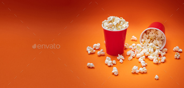 Pop corn scattered on orange color background, top view - Stock Photo - Images