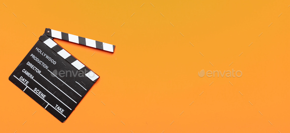 Movie clapperboard on orange color background, banner, top view - Stock Photo - Images