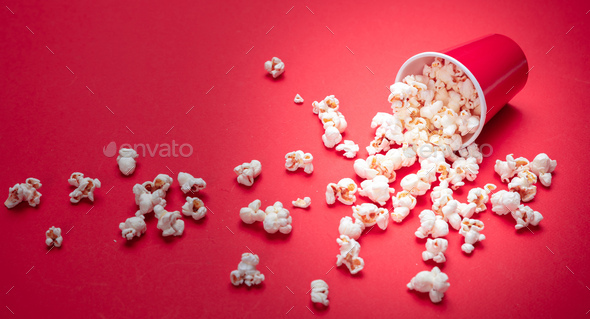 Pop corn scattered on red color background, closeup view - Stock Photo - Images
