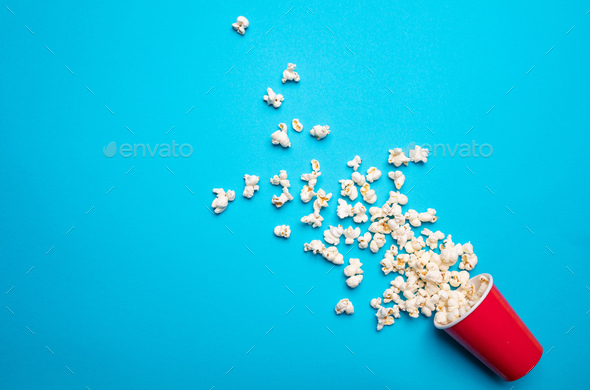 Pop corn scattered on blue color background, top view - Stock Photo - Images