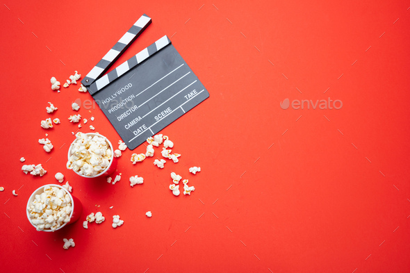 Clapperboard and pop corn on red color background, top view - Stock Photo - Images