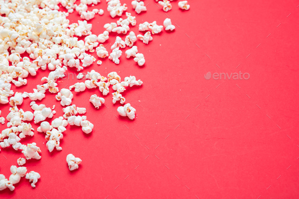 Pop corn scattered on red color background, top view - Stock Photo - Images