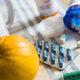 Medication during breakfast, capsules next to a orange, conceptual image - PhotoDune Item for Sale