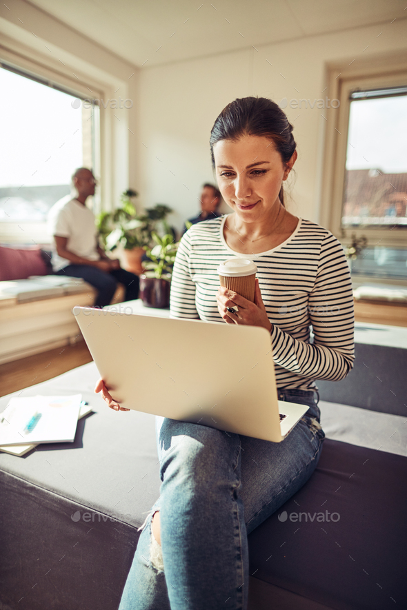 Businesswoman working online and enjoying a coffee on her break - Stock Photo - Images