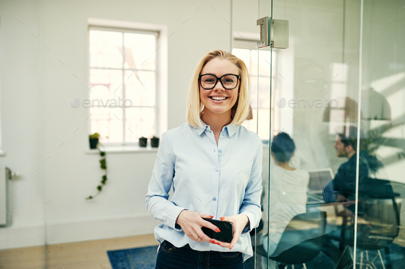 Smiling young businesswoman standing in a modern office - Stock Photo - Images
