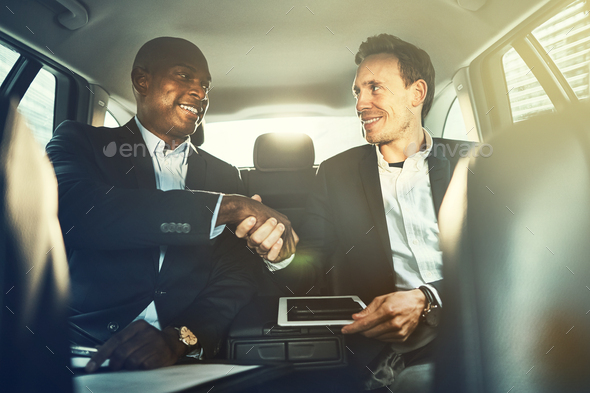 Businessmen shaking hands together in the backseat of a car - Stock Photo - Images