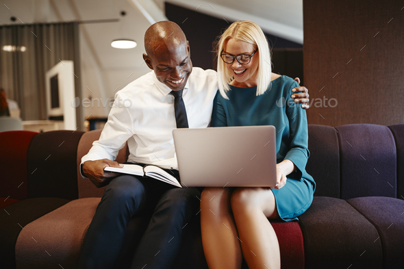 Excited coworkers sitting on an office sofa working online - Stock Photo - Images