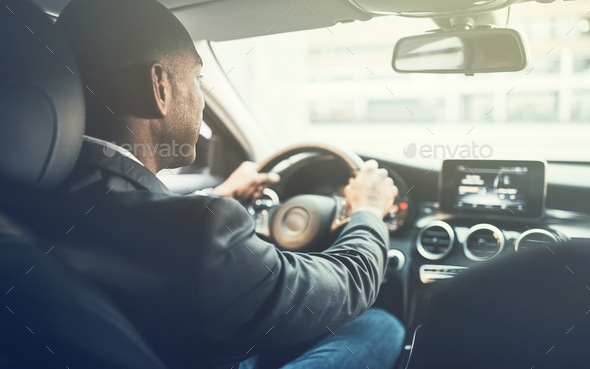 Young African man driving a car through the city - Stock Photo - Images