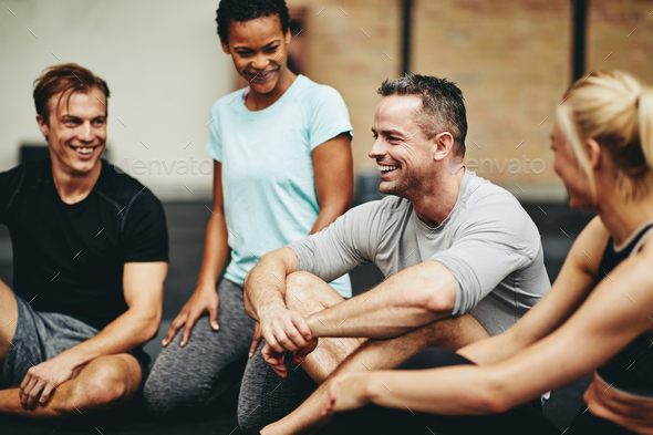 Diverse friends laughing on a gym floor after working out - Stock Photo - Images