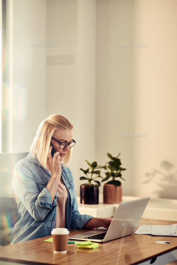 Focused young businesswoman talking on a cellphone in her office - Stock Photo - Images