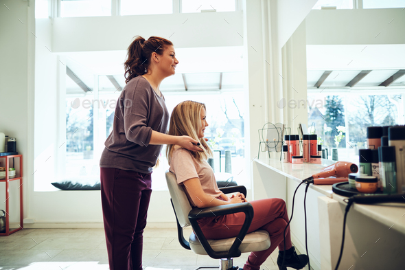 Smiling hairdresser finishing a female client's haircut in her salon - Stock Photo - Images