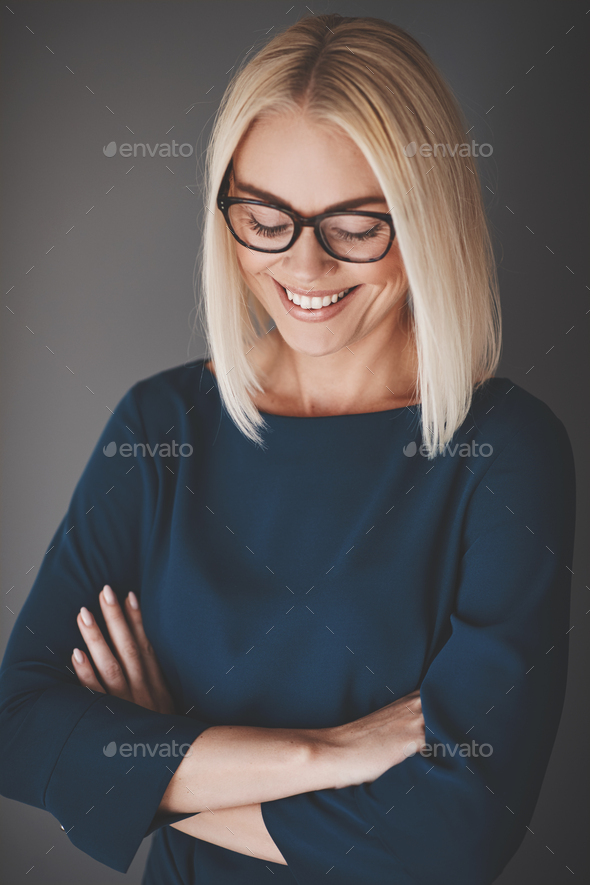Young businesswoman standing with arms crossed against a gray background - Stock Photo - Images