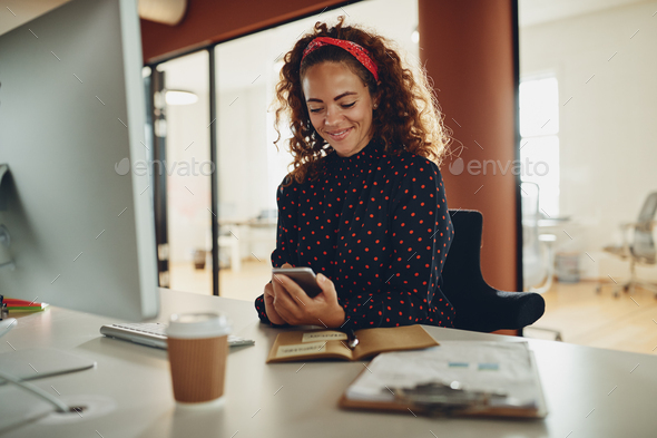 Young businesswoman sitting at her desk reading a text message - Stock Photo - Images