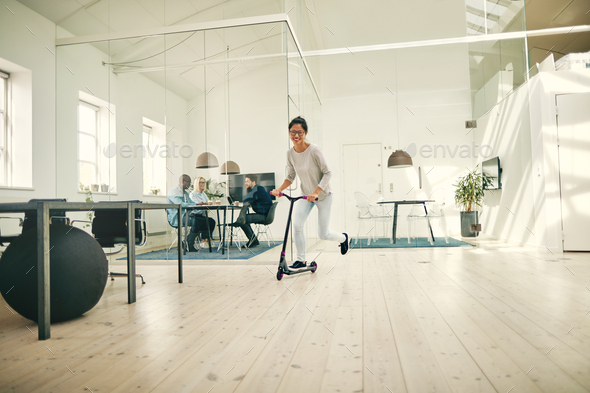 Smiling young Asian businesswoman riding a scooter around an office - Stock Photo - Images