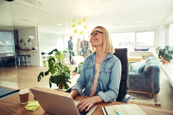 Smiling young businesswoman working on a laptop in an office - Stock Photo - Images