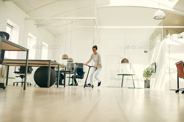 Laughing young Asian businesswoman riding a scooter around an office - Stock Photo - Images