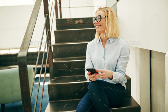 Smiling businesswoman using her cellphone while sitting on office stairs - Stock Photo - Images