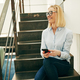 Smiling businesswoman using her cellphone while sitting on office stairs - PhotoDune Item for Sale