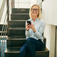 Laughing businesswoman sitting on office stairs reading a funny text - PhotoDune Item for Sale