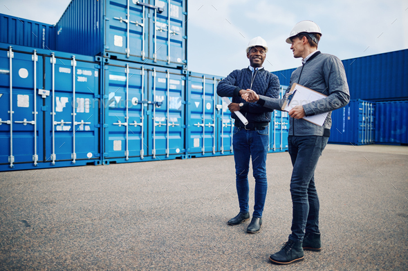 Smiling engineers shaking hands together in a shipping yard - Stock Photo - Images