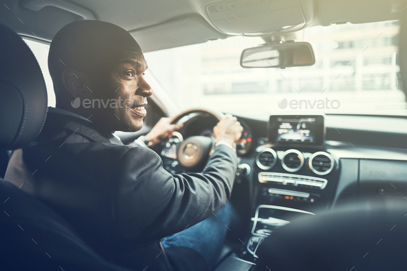 Smiling young African man driving through the city - Stock Photo - Images