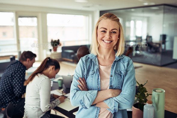 Young businesswoman smiling with coworkers sitting in the background - Stock Photo - Images