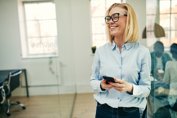 Laughing young businesswoman standing with her cellphone at work - Stock Photo - Images