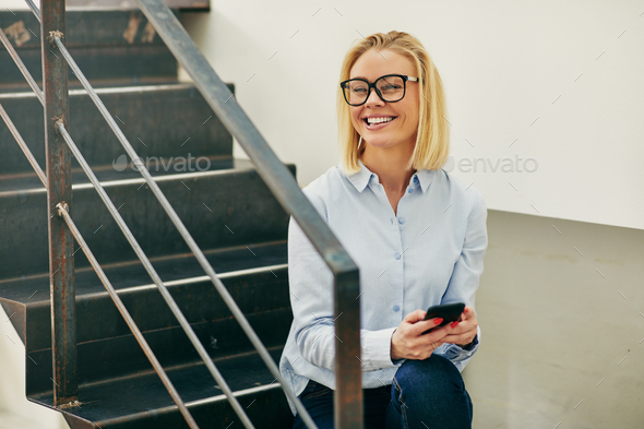 Laughing young businesswoman sitting on office stairs reading text messages - Stock Photo - Images