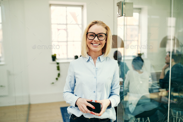 Smiling young businesswoman holding her cellphone in an office - Stock Photo - Images