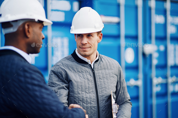 Two engineers shaking hands together in a shipping yard - Stock Photo - Images
