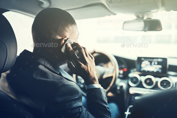 African businessman driving in the city talking on his cellphone - Stock Photo - Images