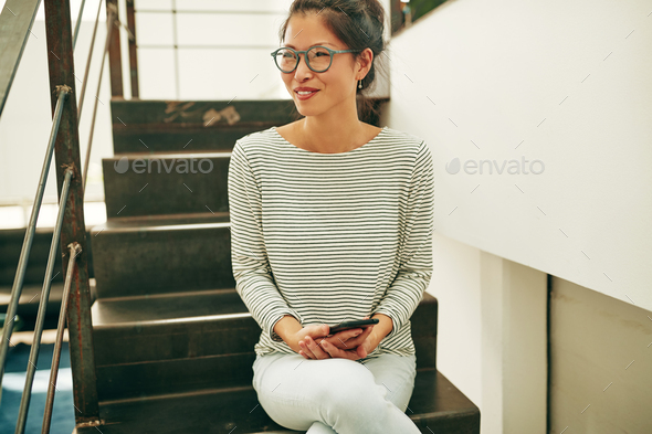 Asian businesswoman smiling while sitting on office stairs reading a text - Stock Photo - Images