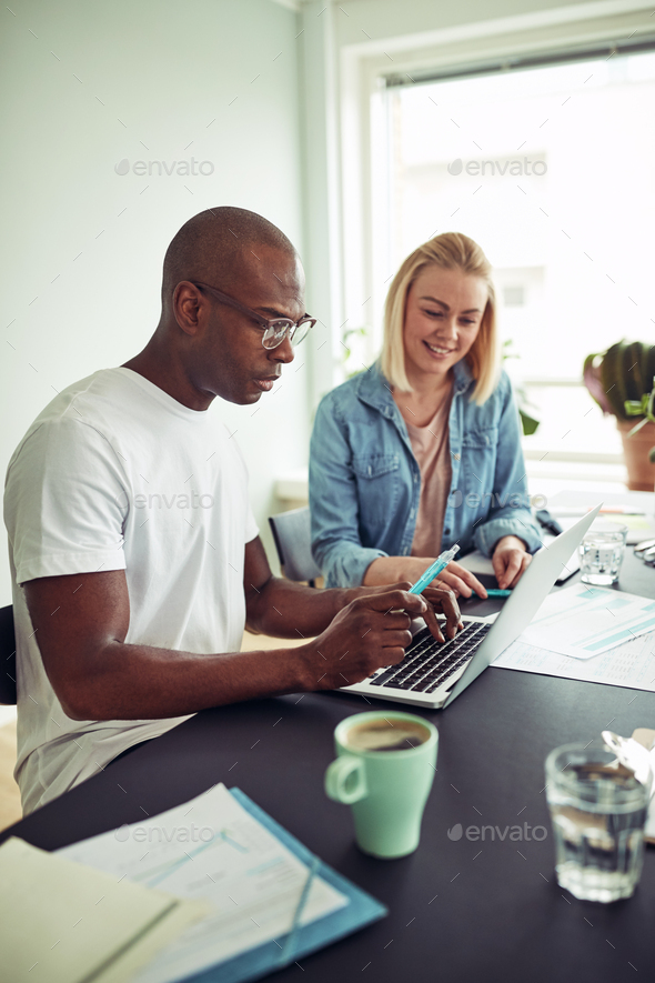 Diverse businesspeople working online with a laptop in an office - Stock Photo - Images
