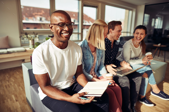 Smiling African businessman sitting with colleagues in a modern office - Stock Photo - Images