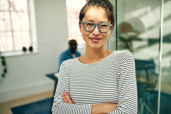 Smiling young Asian businesswoman standing in a bright office - Stock Photo - Images