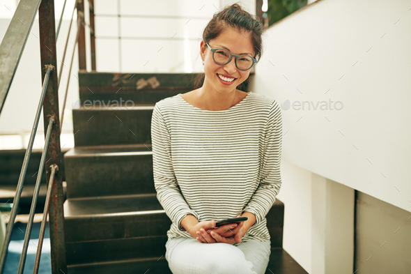 Smiling Asian businesswoman sitting on stairs reading a text message - Stock Photo - Images