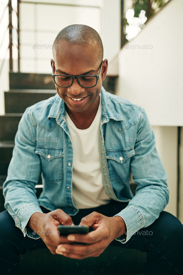 Smiling young African businessman sitting on office stairs text messaging - Stock Photo - Images