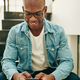Smiling young African businessman sitting on office stairs text messaging - PhotoDune Item for Sale