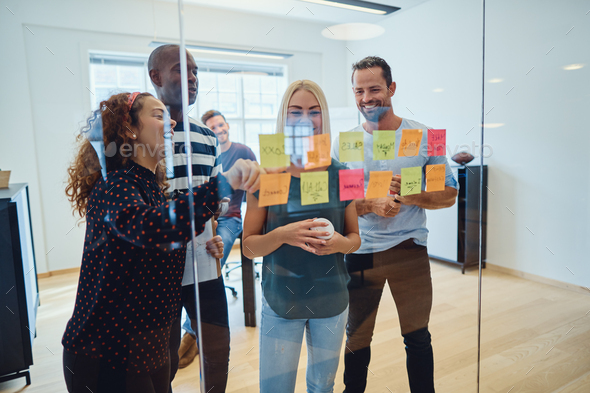Designers laughing together while brainstorming ideas in an office - Stock Photo - Images