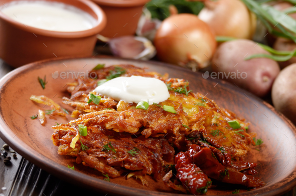 Closeup view at Homemade tasty potato pancakes in clay dish with - Stock Photo - Images