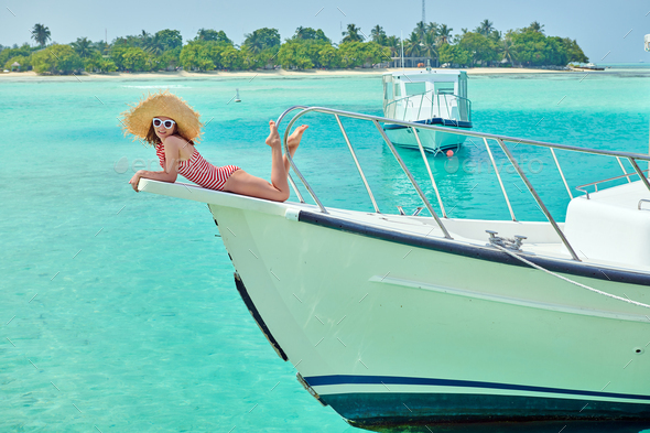 Woman in red bikini lying on boat bow - Stock Photo - Images