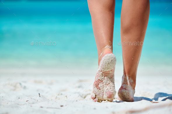 Woman walking on tropical white sand beach - Stock Photo - Images
