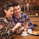 Beautiful wife and husband look at the phone while having dinner - PhotoDune Item for Sale