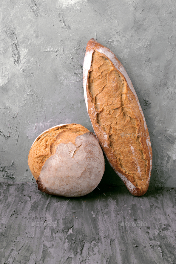 rustic loaves of bread supported on gray marbled background - Stock Photo - Images