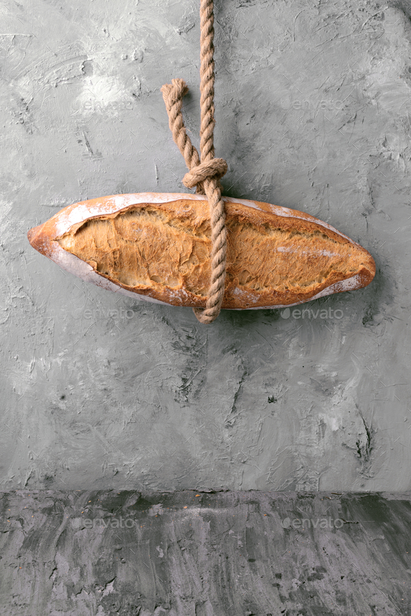loaf of bread hanging on a rope, in front of gray marbling background - Stock Photo - Images