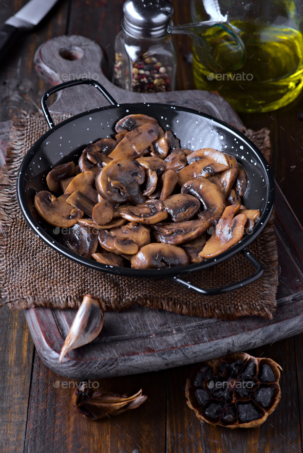 portion of cut fried mushrooms, in metal frying pan on wood - Stock Photo - Images