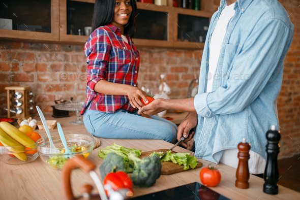 Black couple cooking together on the kitchen - Stock Photo - Images