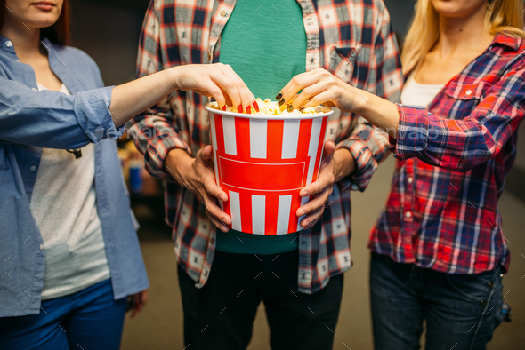 Group of friends poses with popcorn in cinema hall - Stock Photo - Images