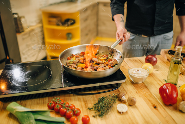 Male chef cooking meat with vetables on fire - Stock Photo - Images