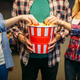 Group of friends poses with popcorn in cinema hall - PhotoDune Item for Sale